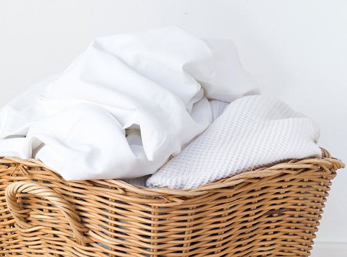 wicker laundry basket filled with laundry