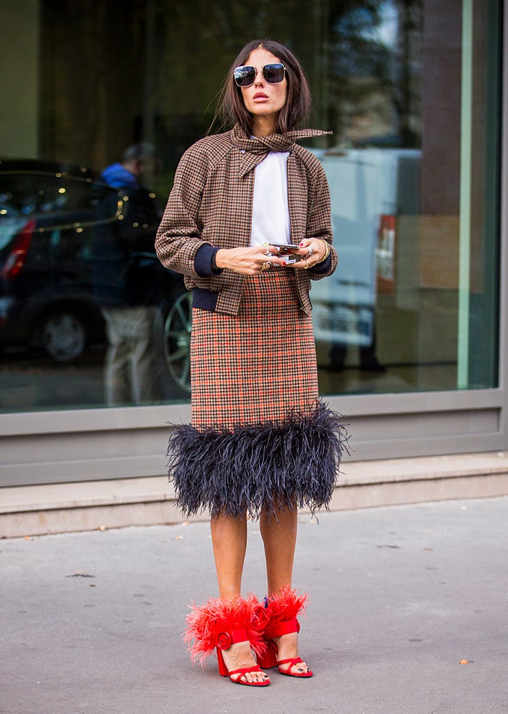woamn wearing a plaid skirt with feathers