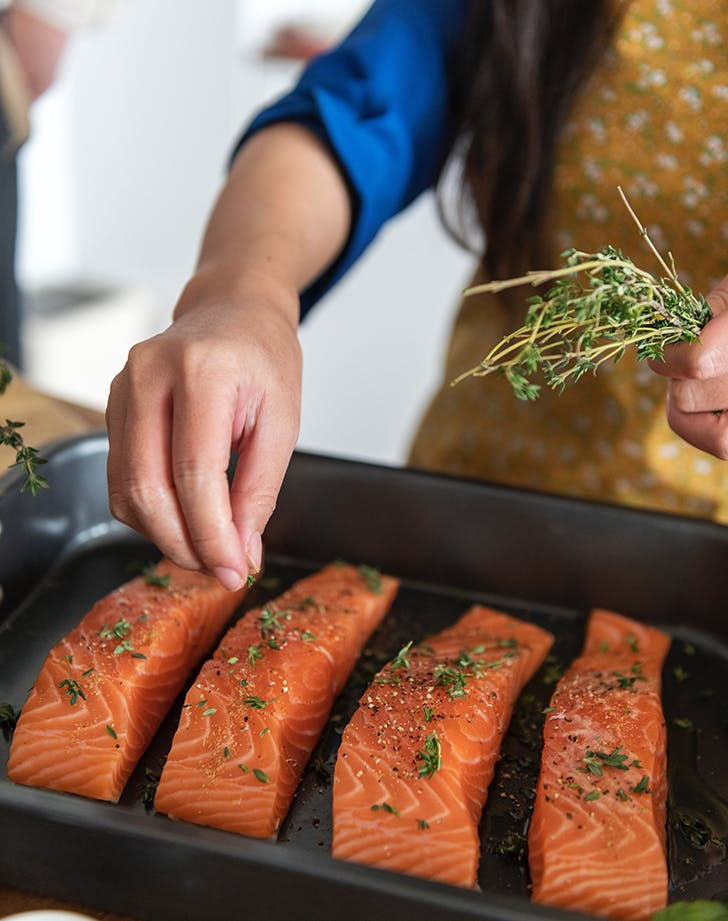 woman seasoning salmon