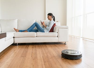 woman sitting on couch while robot vacuum cleans 400