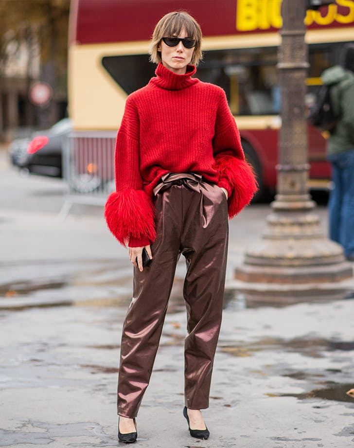 woman wearing a feathered sweater with satin pants