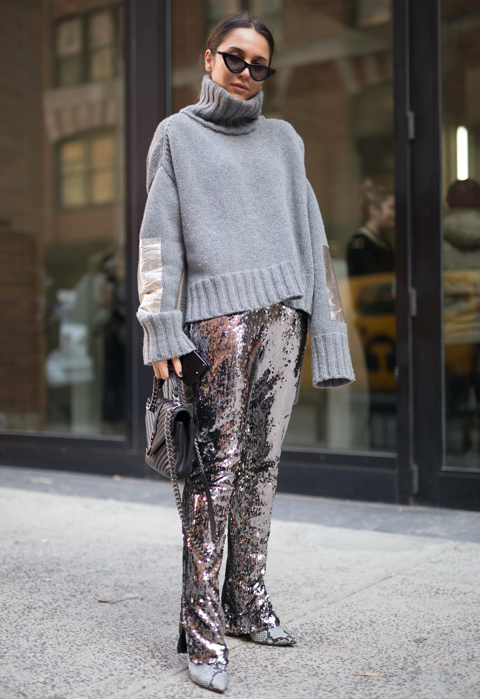 woman wearing a gray sweater and sequin pants