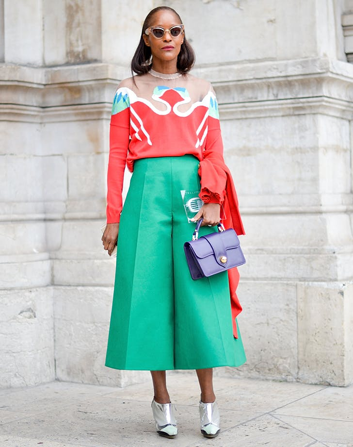 woman wearing green culottes and a patterned sweater