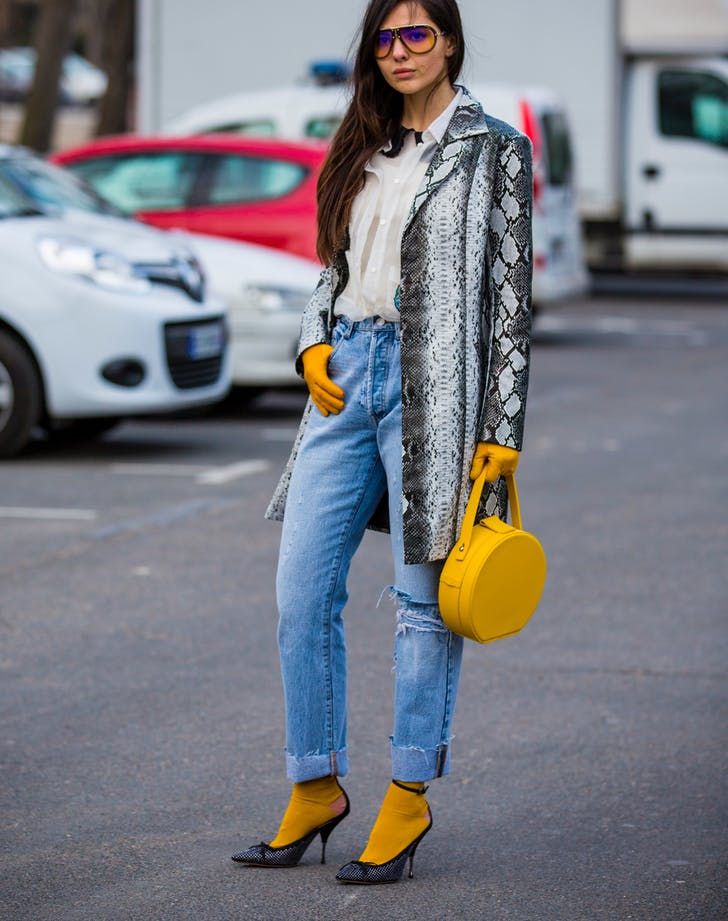 2025c124387 woman wearing jeans and a snake print coat