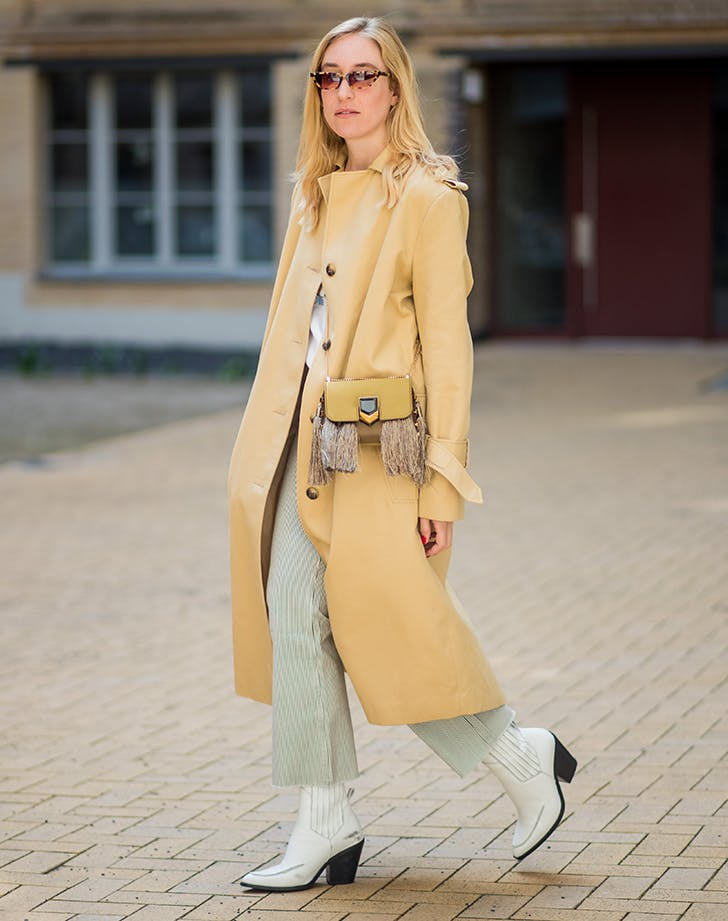 woman wearing white cowboy boots with a yellow coat