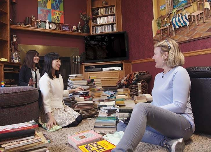 Marie Kondo with pile of books on floor