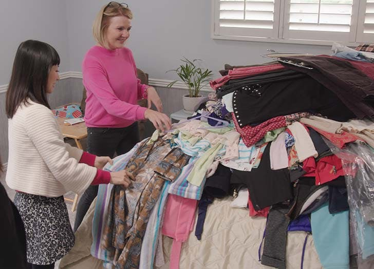 Marie Kondo with pile of clothes on bed