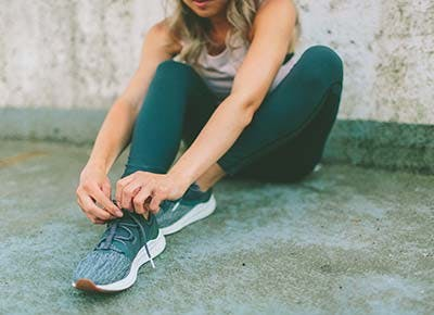 Woman with DOMS tying workout shoes 400