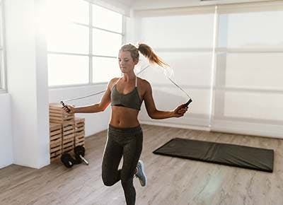 Woman working out jumping jump rope 400