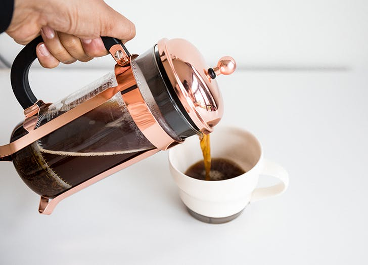 a pot of french press coffee is being poured into a coffee mug the french press is rose gold