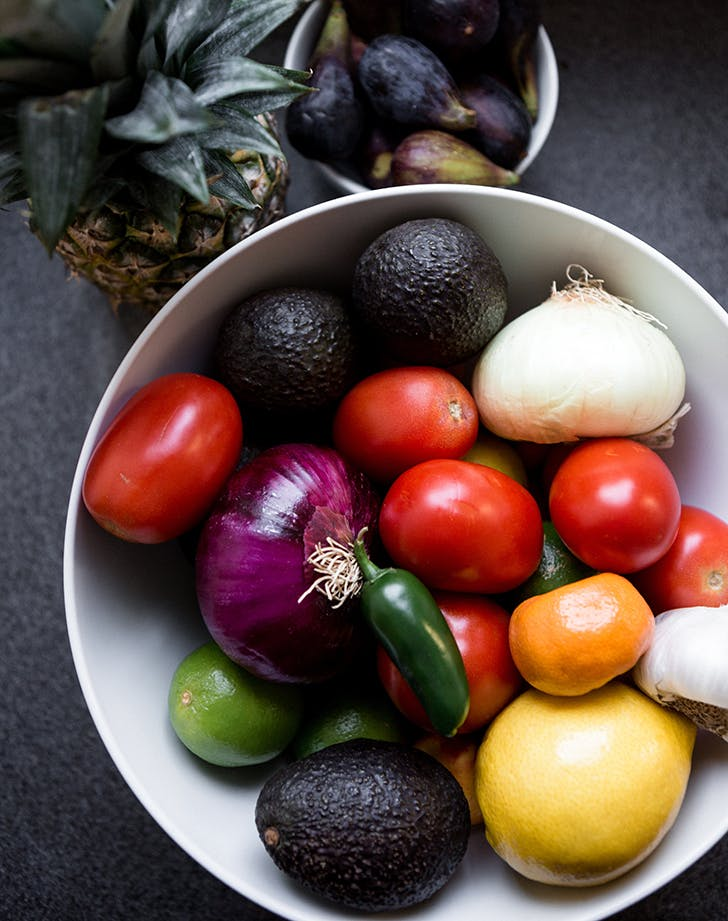 a white bowl full of bright and colorful tropical fruits and vegetables sits on a dark table tomato