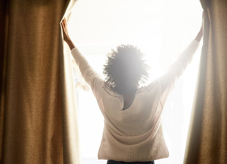 woman opening up curtains