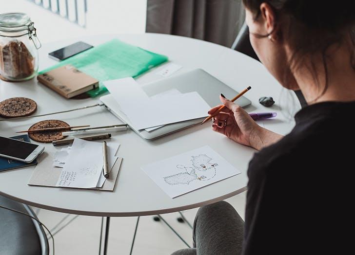 woman sketching map at table
