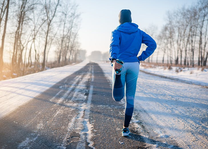 woman stretching before running in the snow