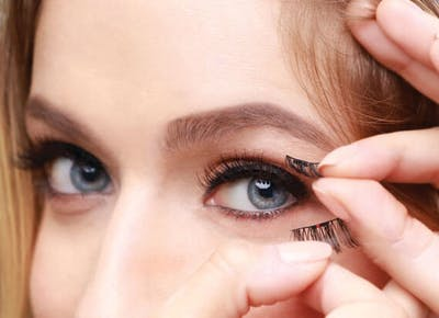 woman putting on magnetic lashes