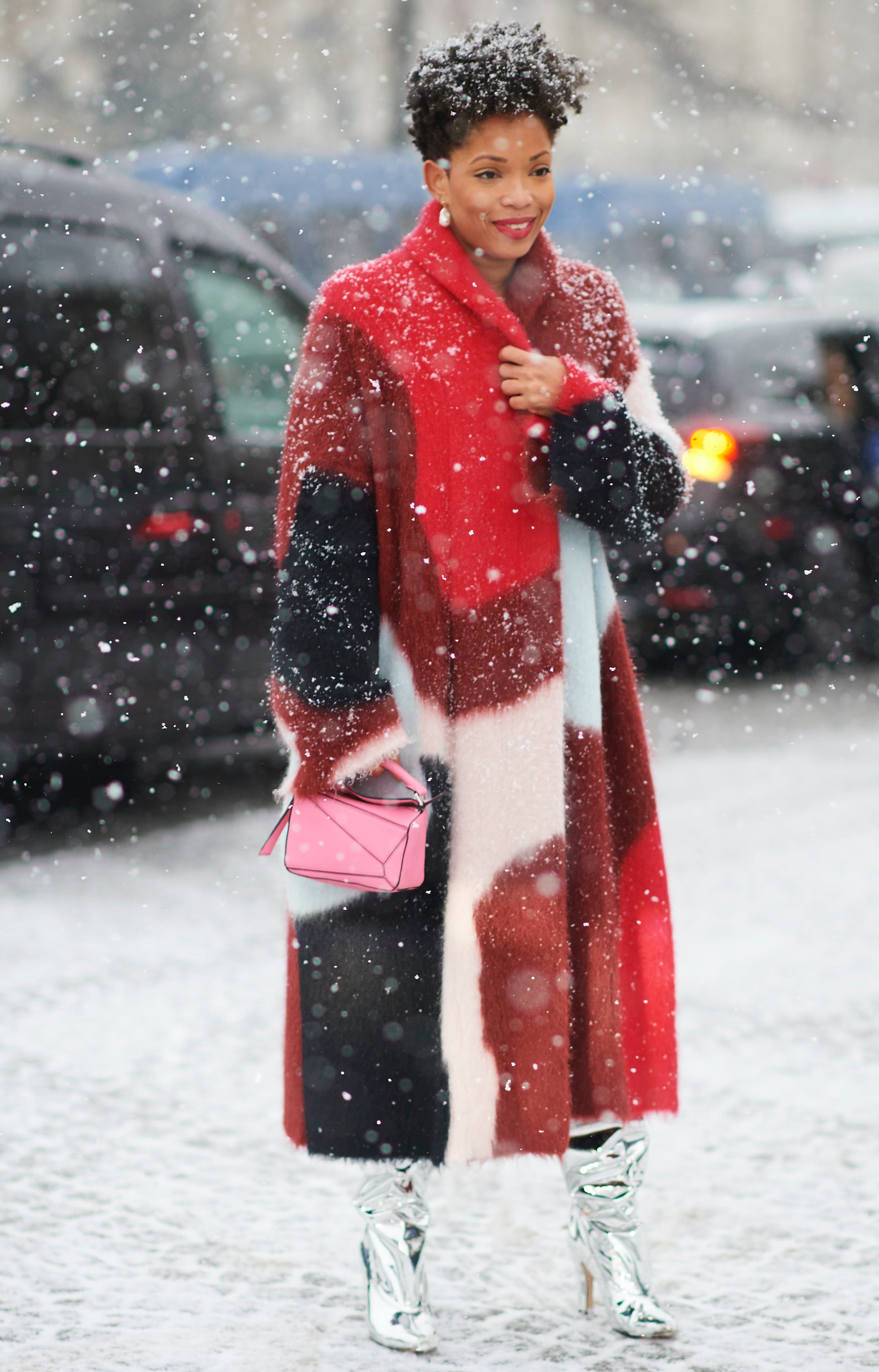 woman wearing a red oversize coat and silver boots in the snow