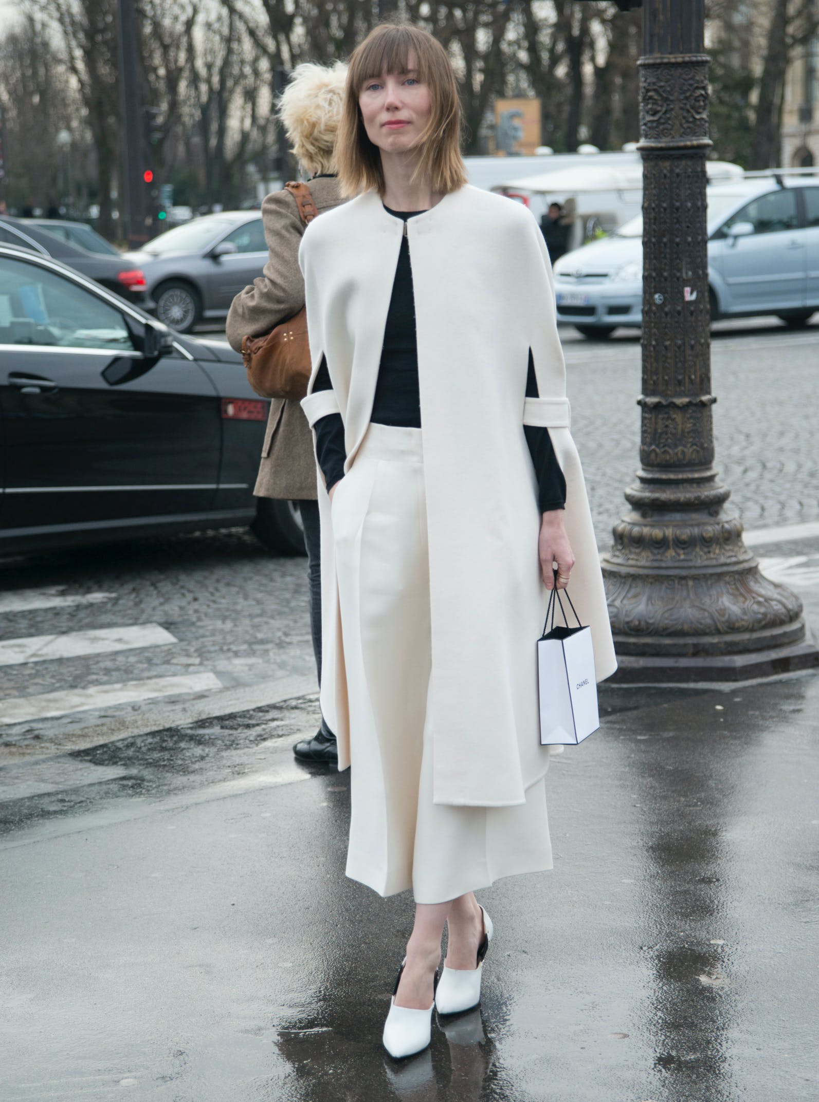 woman wearing a white cape and black top