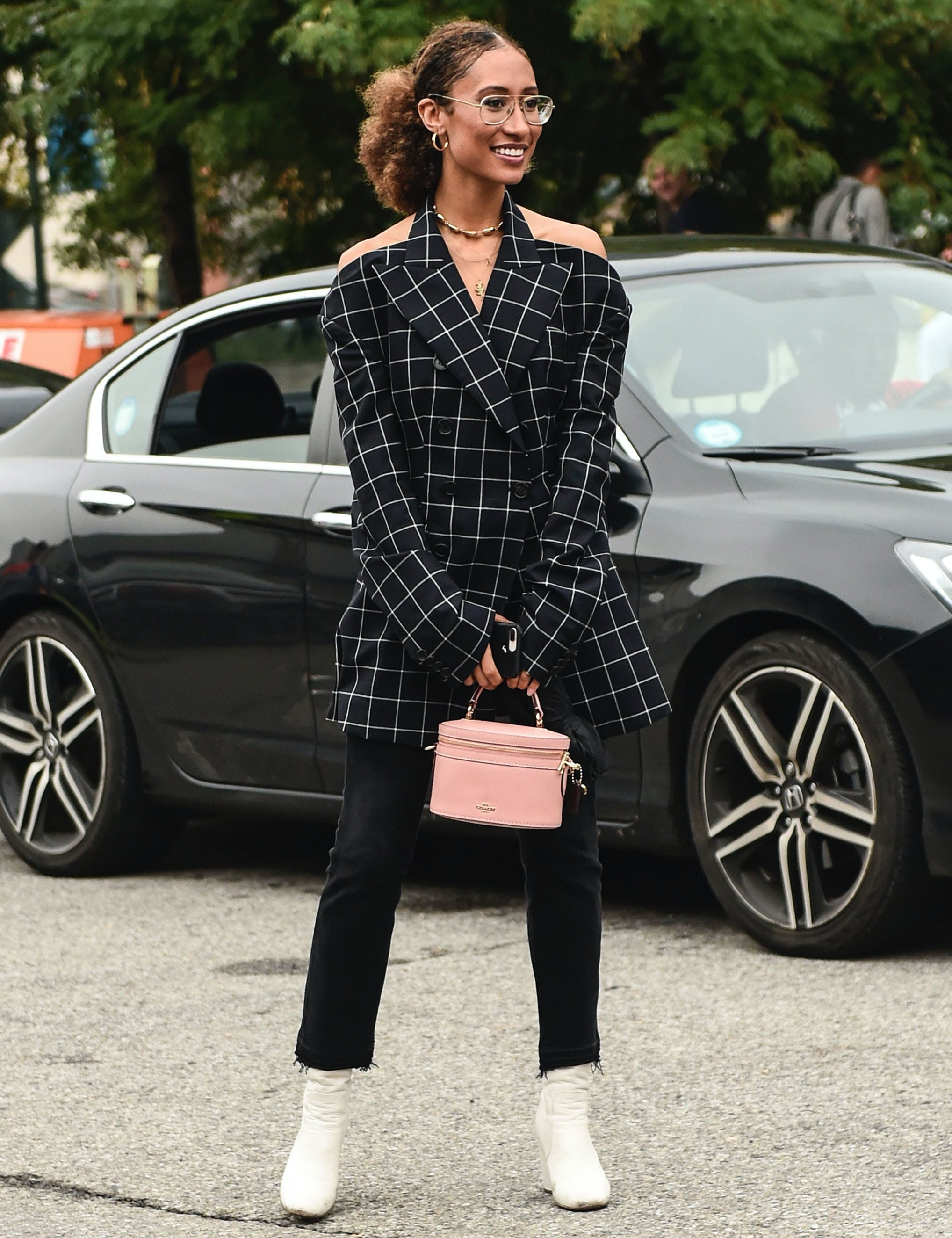 woman wearing black and white with a pink handbag