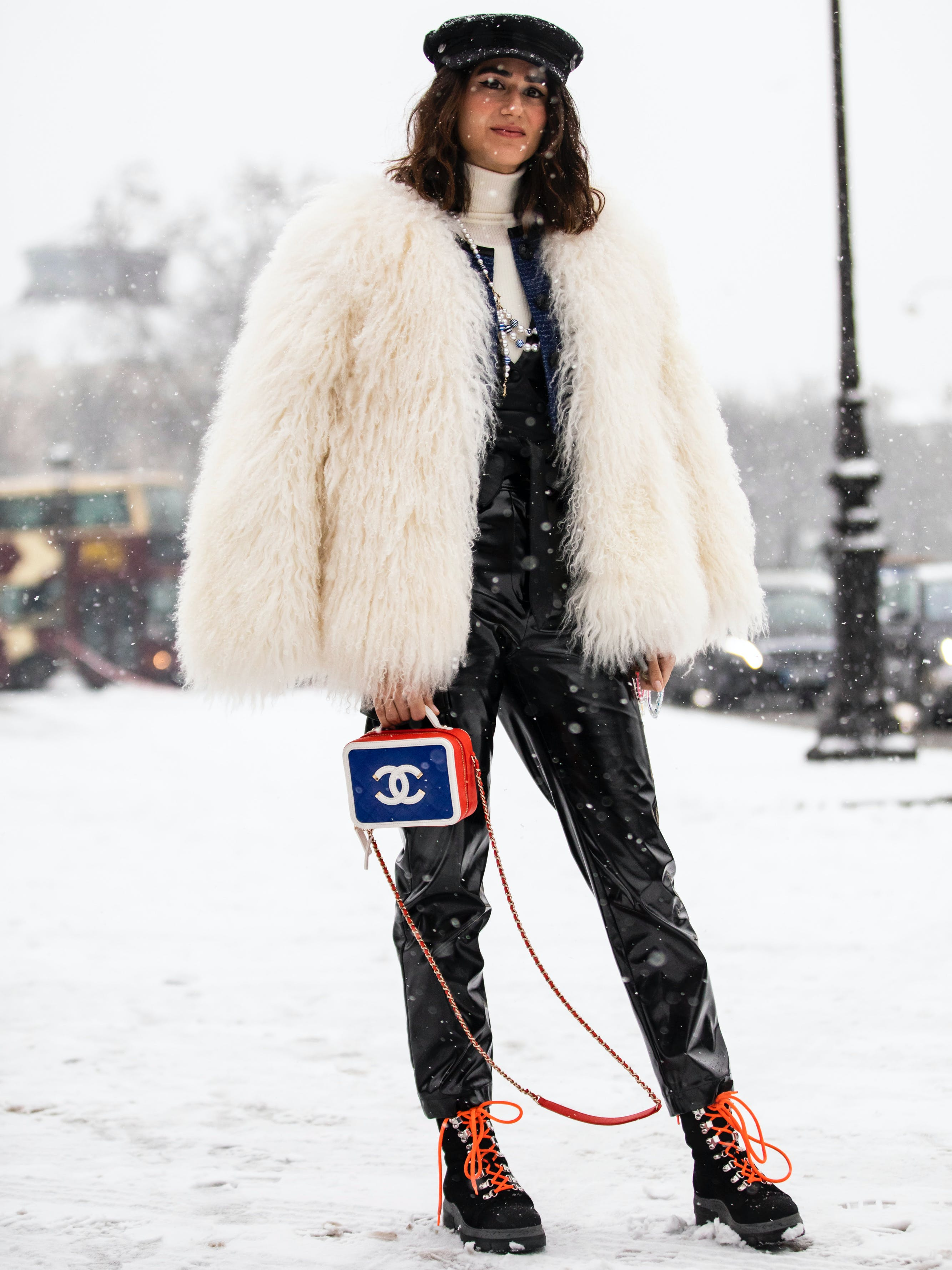 woman wearing leather pants and a white faux fur coat