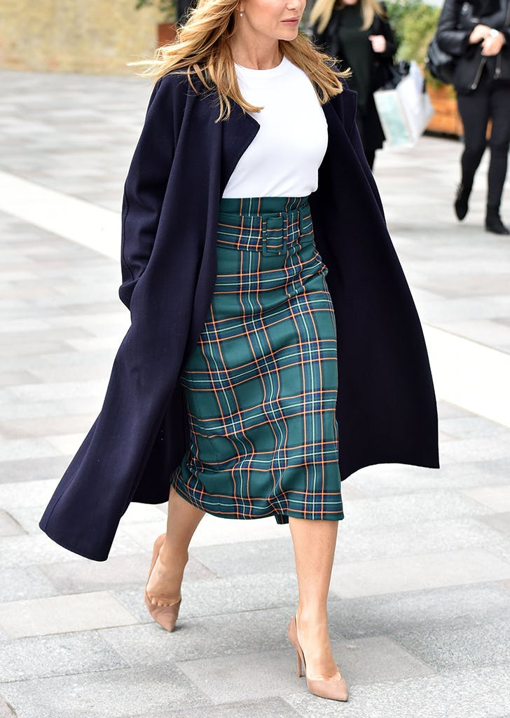 woman wearing a midi skirt and nude pumps
