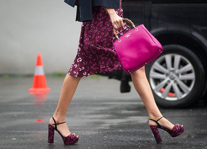 woman carrying a fuscia pink handbag