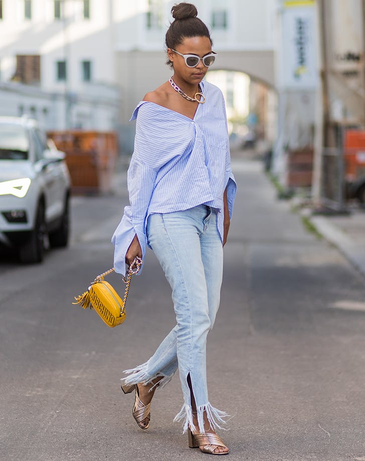 woman wearing an off the shoulder top and fringe hem jeans