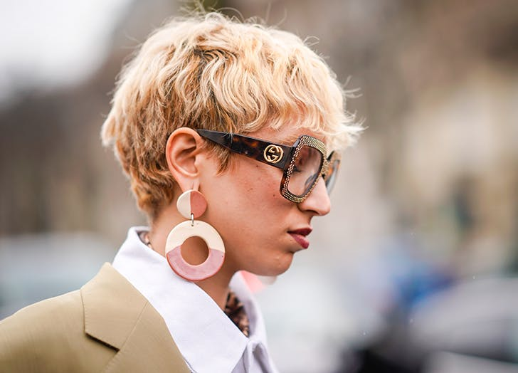 woman wearing funky retro earrings and oversize sunglasses