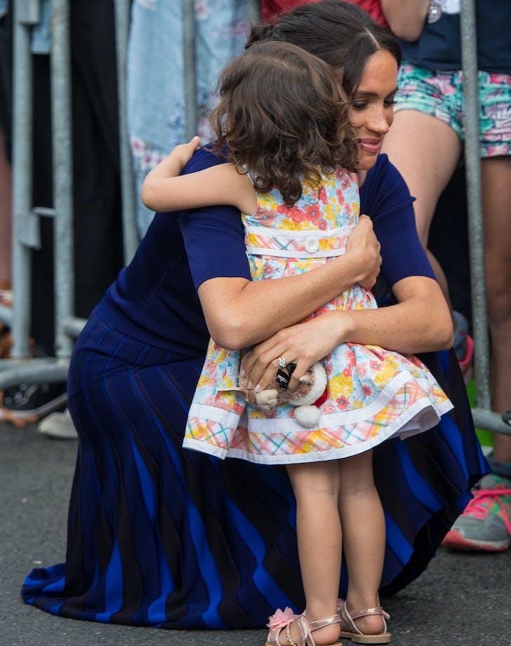 Meghan Markle hugging a little girl