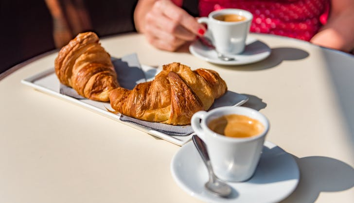 a woman eating croissants at a french cafe