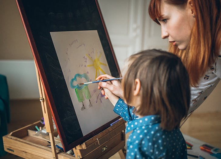 kid painting with babysitter
