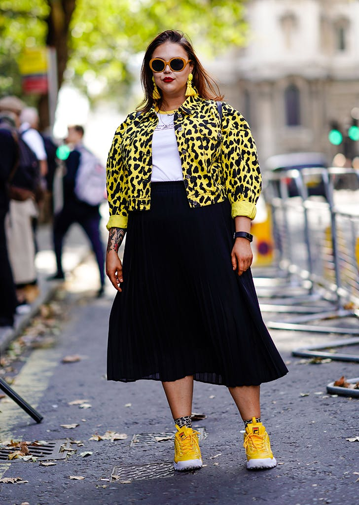 woman wearing a black skirt and yellow printed jacket