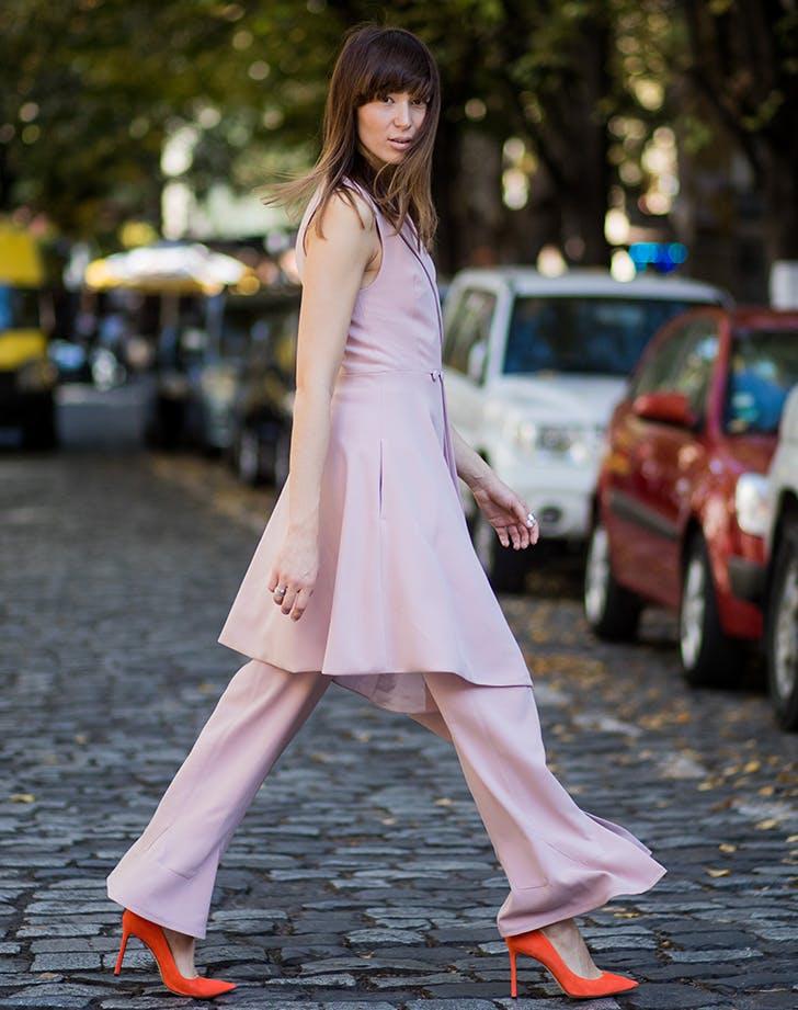 woman walking across the street wearing pink and orange