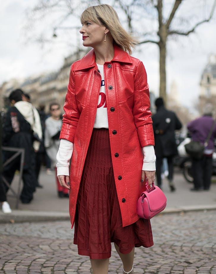 woman wearing red and carrying a pink handbag