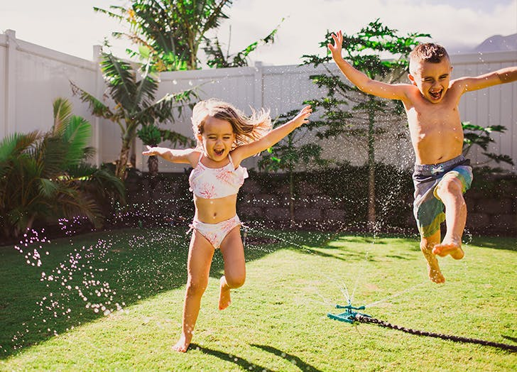 kids in backyard sprinkler