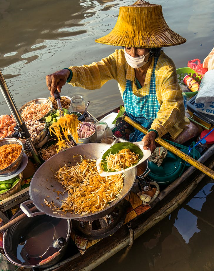 someone selling food off a boat in bangkok
