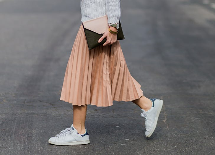 woman wearing white sneakers and pink skirt