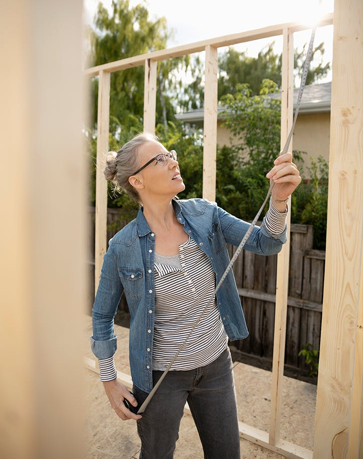 woman measuring a house