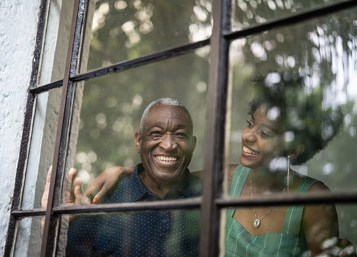 Father and daughter laughing in window