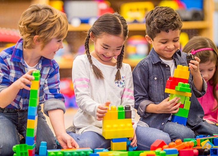 Group of preschoolers in cooperatie type of play with blocks