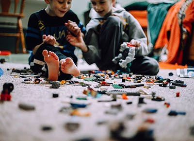 Kids playing with Lego on the floor 400