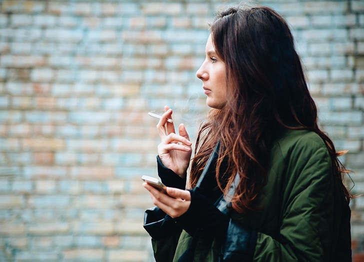 Woman smoking cigarette outside