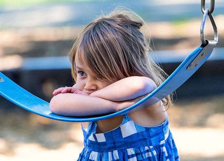 Young girl resting on swing in onlooker type of play