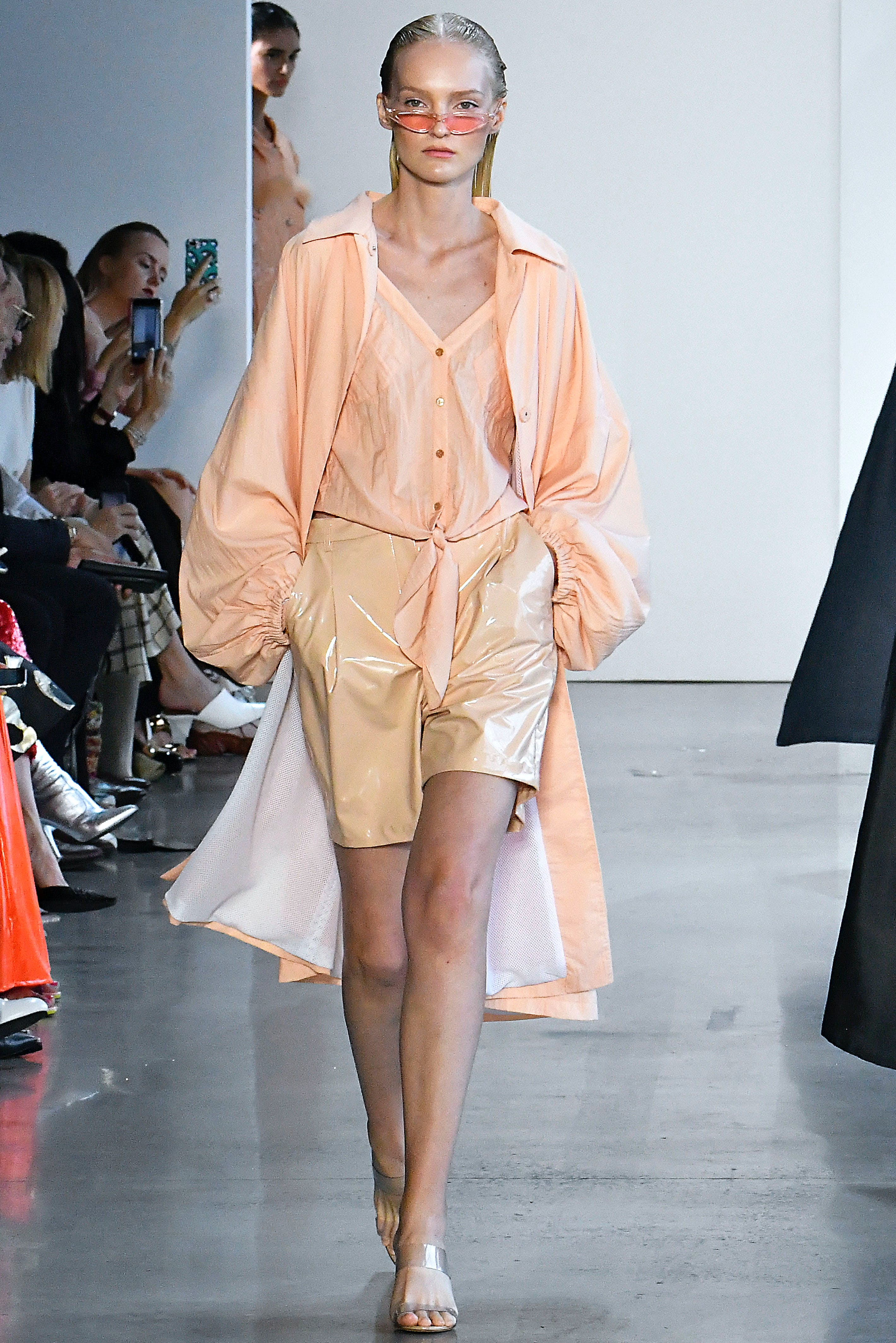model at Sally LaPointe wearing bermuda shorts and a trench coat
