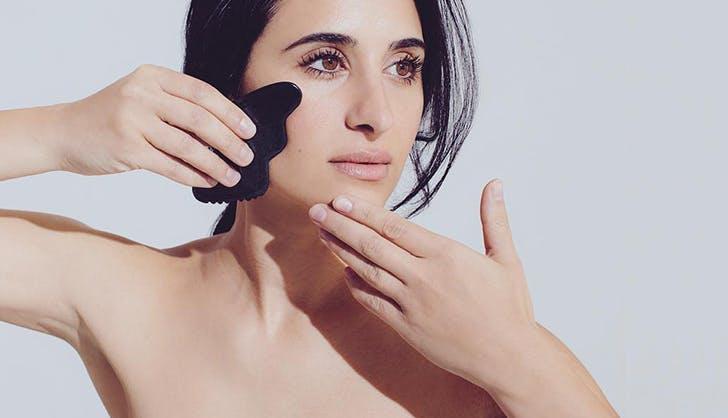 woman doing gua sha facial massage