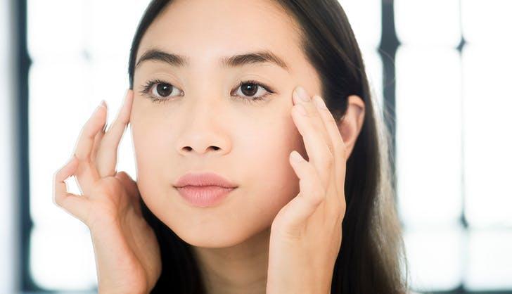 woman giving herself an eye facial massage