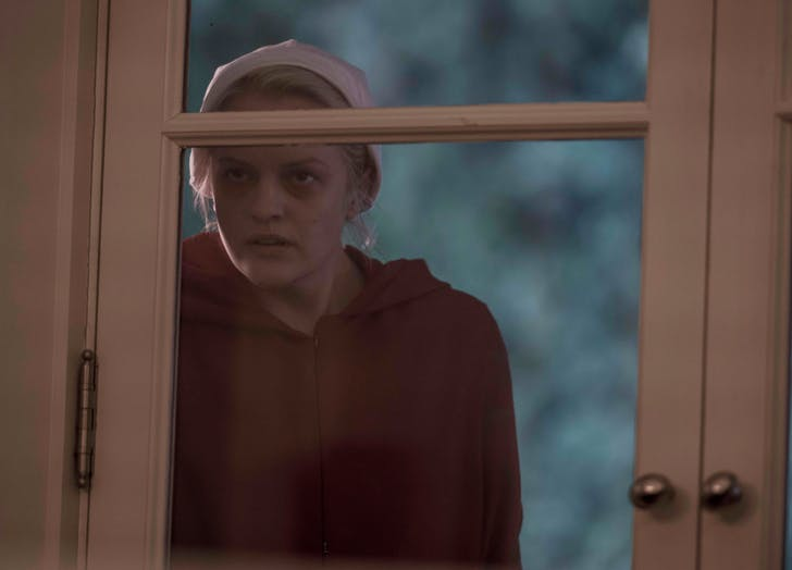 Ofred peering in a window handmaids tale