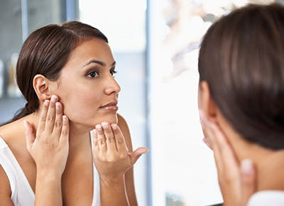 woman looking at face in mirror 400
