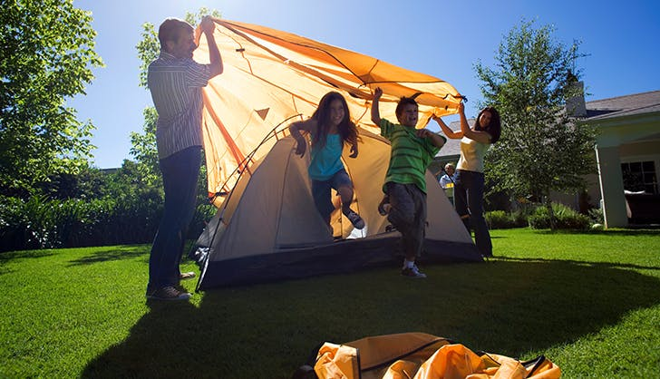 a family setting up a tent in the backyard