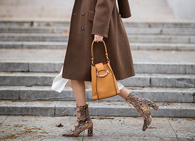 woman in brown coat holding handbag hero
