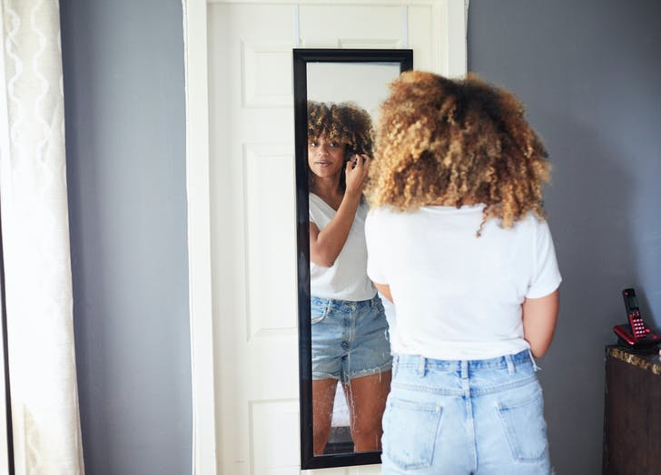 woman putting makeup on in a mirror